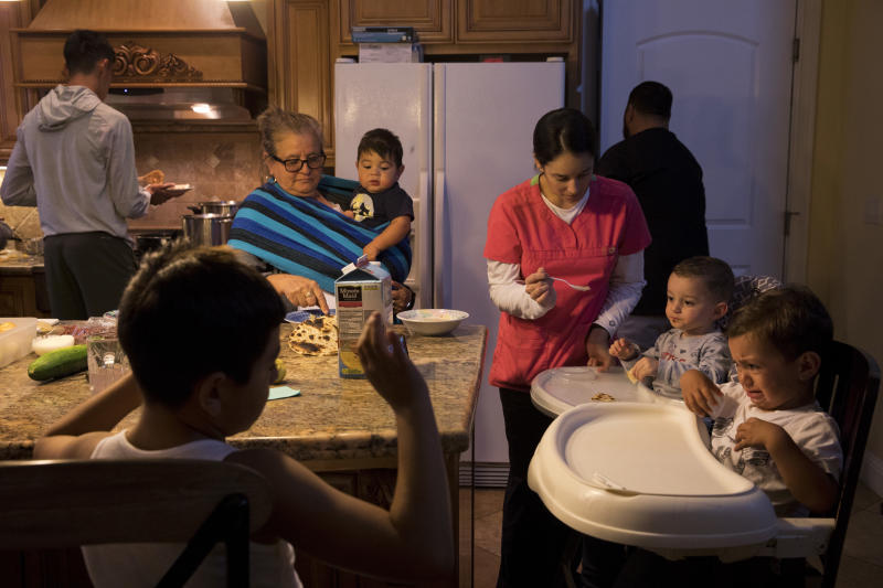 CORRECTS NAME TO SASHA NUNEZ FROM ARACELI NUNEZ - In this Thursday, Sept. 6, 2018, photo, Lilia Coyt, center left, and Coyt's daughter-in-law, Sasha Nunez, feed babies in their four-bedroom home, where three generations and 15 members of the family are jammed into, in Salinas, Calif. Few cities exemplify California's housing crisis better than Salinas, an hour's drive from Silicon Valley and surrounded by farm fields. It's one of America's most unaffordable places to live, and many residents believe politicians lack a grip on the reality of the region's housing crisis. (AP Photo/Jae C. Hong)