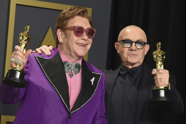 """Elton John, left, and Bernie Taupin, winners of the award for best original song for """"(I'm Gonna) Love Me Again"""" from """"Rocketman"""", pose in the press room at the Oscars on Sunday, Feb. 9, 2020, at the Dolby Theatre in Los Angeles. (Photo by Jordan Strauss/Invision/AP)"""