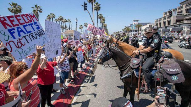PHOTO: Mounted police line up to keep protesters on the sidewalk during a rally to call on California Governor Gavin Newsom to relax the state's stay-at-home orders under COVID-19 in Huntington Beach, Calif., May 1, 2020. (Los Angeles Times via Getty Images, FILE)