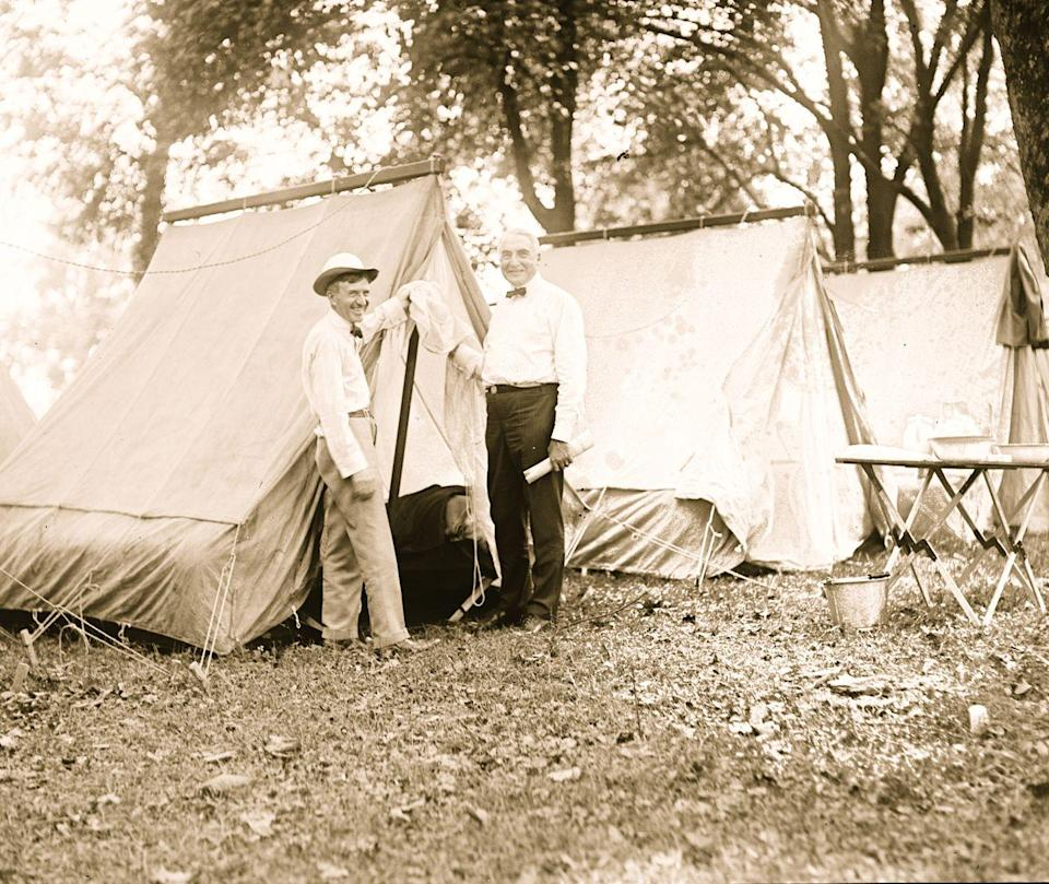 <p>Warren G. Harding smiles as he and the founder of the Firestone Tire and Rubber Company, Harvey Firestone, pose near their tents during a camping trip in 1921. </p>