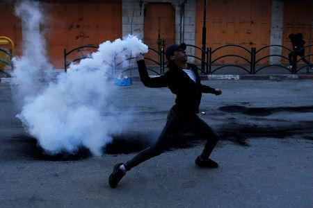 A Palestinian protester returns a tear gas canister fired by Israeli troops during clashes in Hebron, in the occupied West Bank March 29, 2019. REUTERS/Mussa Qawasma