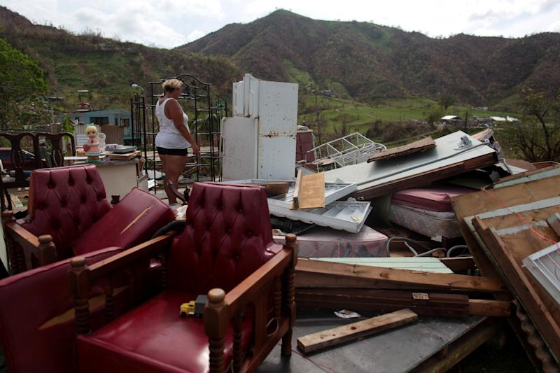 Haydee Mestre looks inside her refrigerator after Hurricane Maria destroyed the town's bridge and the surrounding areas, in San Lorenzo, Morovis, Puerto Rico, October 5, 2017. (Alvin Baez/Reuters)