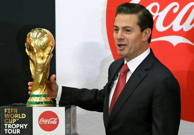 Mexican President Enrique Pena Nieto holds up the FIFA World Cup trophy as part of a global tour during a ceremony at Los Pinos presidential residence in Mexico City, Mexico April 11, 2018. REUTERS/Henry Romero