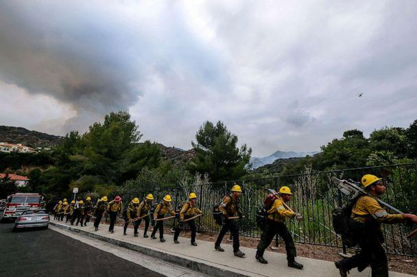 PHOTO: Members of the Hotshots fire crew walk in line during a wildfire in the Pacific Palisades area of Los Angeles, May 16, 2021. (Ringo H.w. Chiu/AP)