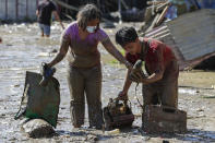 Residents carry belongings from their homes at the typhoon-damaged Kasiglahan village in Rodriguez, Rizal province, Philippines, Friday, Nov. 13, 2020. Thick mud and debris coated many villages around the Philippine capital Friday after Typhoon Vamco caused extensive flooding that sent residents fleeing to their roofs and killing dozens of people. (AP Photo/Aaron Favila)