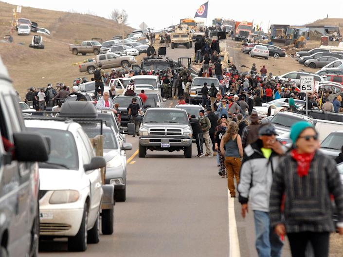<p>An exodus of Dakota Access Pipeline protesters move south on Highway 1806 as a line of law enforcement slowly push the protest effort from the Front Line Camp to the Oceti Wakoni overflow camp a few miles down the road in Morton County, N.D., Thursday, Oct. 27, 2016. (Photo: Mike McCleary/The Bismarck Tribune via AP) </p>