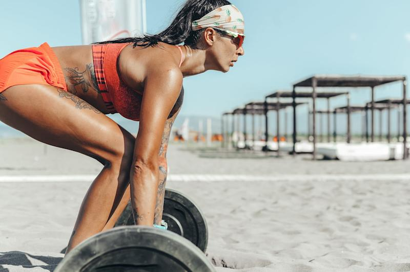 Strong and confident female athlete working out on the beach. Miami, USA