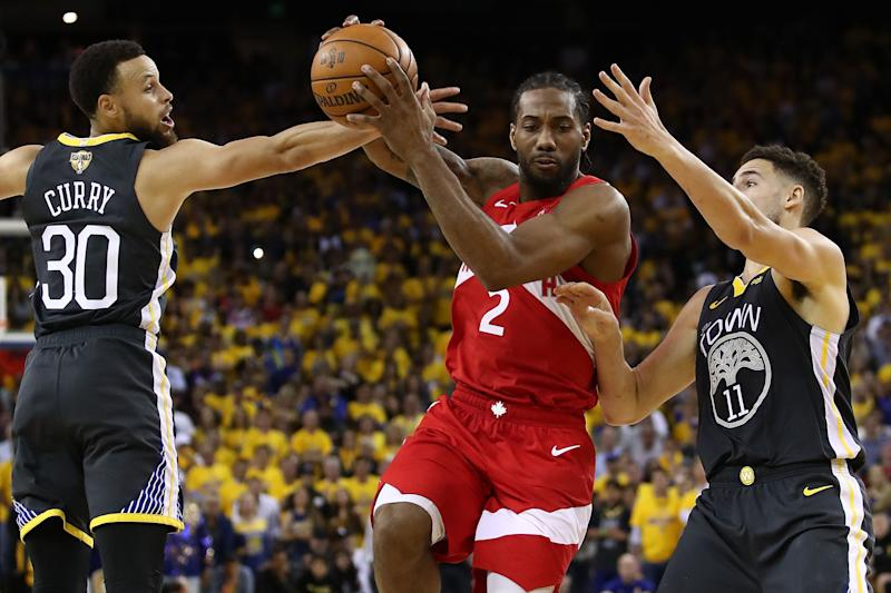 Kawhi Leonard #2 of the Toronto Raptors drives to the basket against Stephen Curry #30 and Klay Thompson #11 of the Golden State Warriors (Photo by Ezra Shaw/Getty Images)