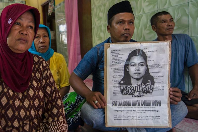 Family members of beheaded Indonesian maid Siti Zainab hold a poster bearing her portrait at their family home in Bangkalan in East Java province (AFP Photo/Juni Kriswanto)