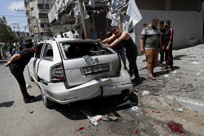 Residents inspect a car that was hit in an Israeli airstrike that killed three people in the car, on the main road in Gaza City, Wednesday, May 12, 2021. (AP Photo/Adel Hana)
