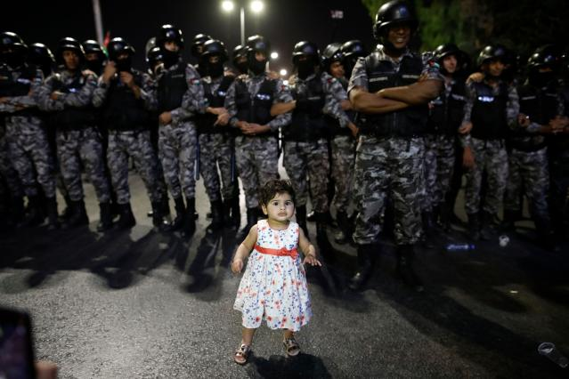 <p>A young girl stands in front of Jordanian anti-riot police during a protest near the prime minister's office in Amman, Jordan, on June 5, 2018. (Photo: Ahmad Gharabli/AFP/Getty Images) </p>