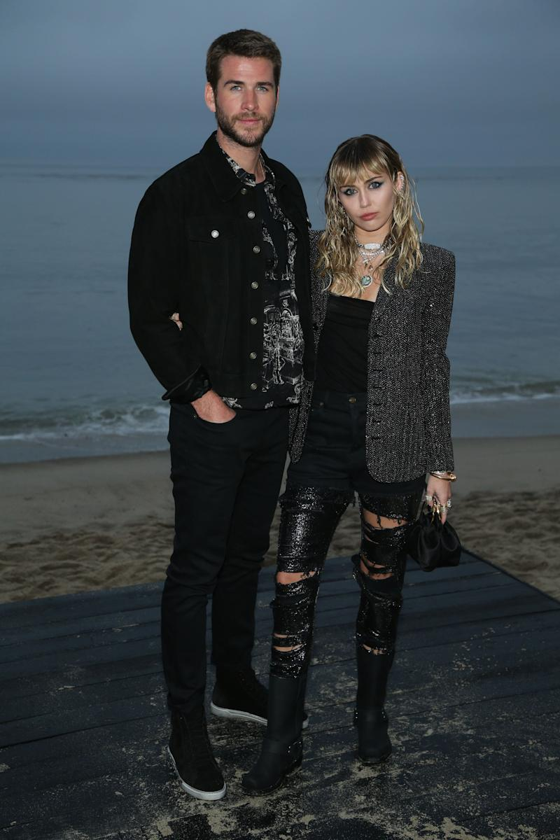 MALIBU, CALIFORNIA - JUNE 06: (L-R) Liam Hemsworth and Miley Cyrus attend the Saint Laurent Mens Spring Summer 20 Show on June 6, 2019 in Malibu, California. (Photo by Phillip Faraone/WireImage,)