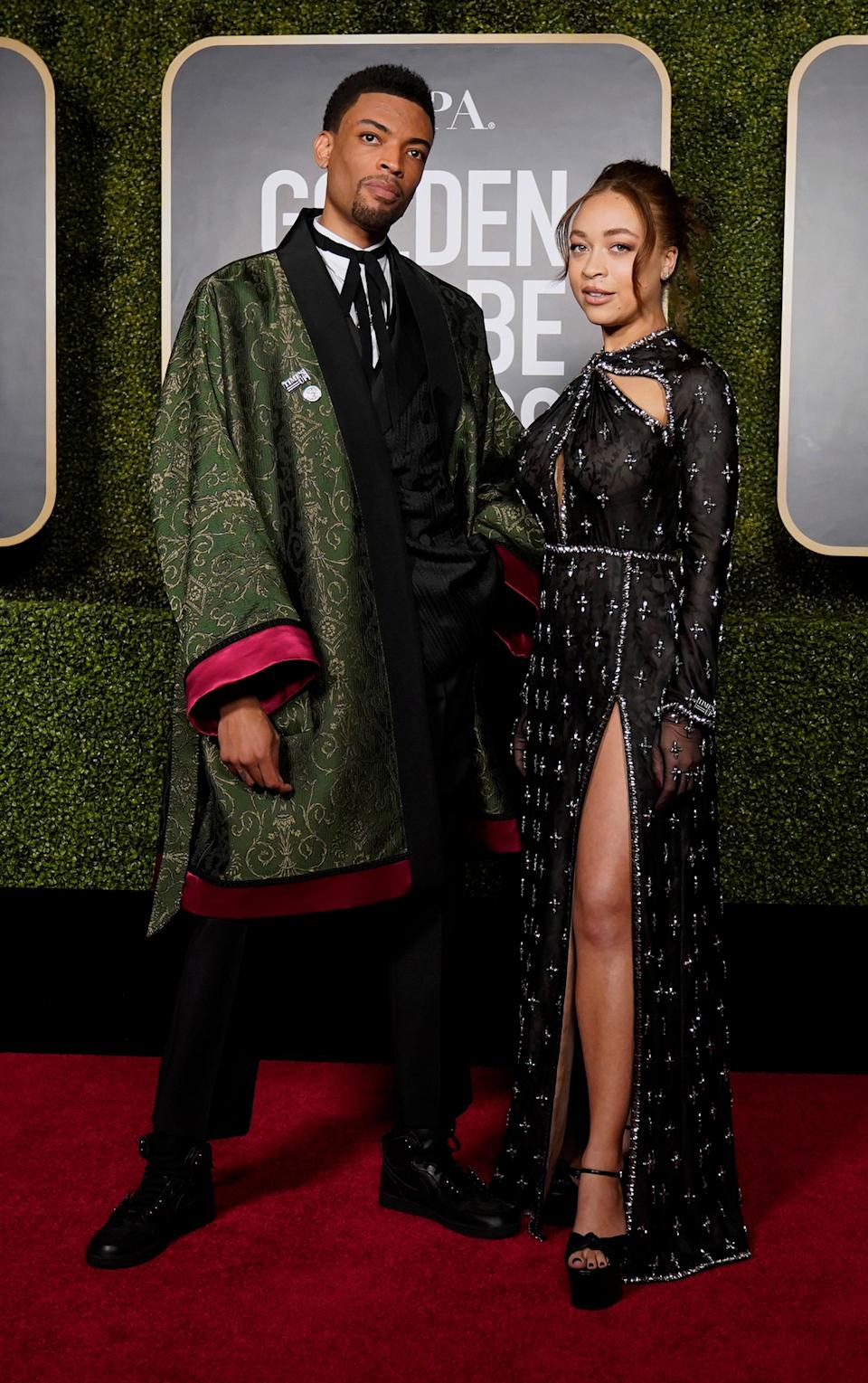 Golden Globe 2021 ambassadors Jackson Lee and Satchel Lee made a red carpet statement. Jackson rocked a patterned overcoat with a Times Up pin, while his sister, Satchel, stunned in an embellished black gown with a high slit.