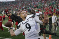Cincinnati quarterback Desmond Ridder (9) throws a football into the stands after Cincinnati defeated Notre Dame, 24-13, in an NCAA college football game, Saturday, Oct. 2, 2021, in South Bend, Ind. (AP Photo/Darron Cummings)
