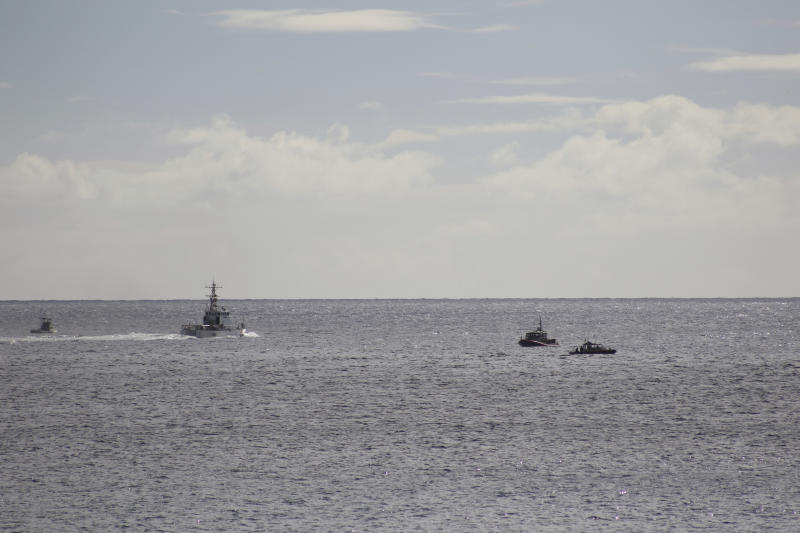A U.S. Coast Guard vessel and other rescue boats respond to a plane crash off Honolulu, Wednesday, Dec. 12, 2018. Federal Aviation Administration spokesman Ian Gregor said a Hawker Hunter jet went down in the ocean around 2:25 p.m. after taking off from Honolulu's airport. A civilian contractor for the Hawaii Air National Guard who was participating in a military exercise survived after his plane crashed off the coast of Honolulu, authorities said Wednesday. U.S. Coast Guard spokeswoman Petty Officer Sara Muir said the pilot is in stable condition after being rescued about 3 miles south of Oahu near Honolulu's Sand Island. (AP Photo/Caleb Jones)