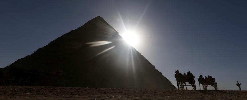 """Tourists ride in horse carriages past one of the Great Pyramids in Giza, Egypt, Wednesday, Dec. 12, 2012. An Egyptian opposition alliance urged supporters on Wednesday to vote """"No"""" in the referendum on a disputed constitution but said it may still boycott if its conditions are not met. (AP Photo/Petr David Josek)"""