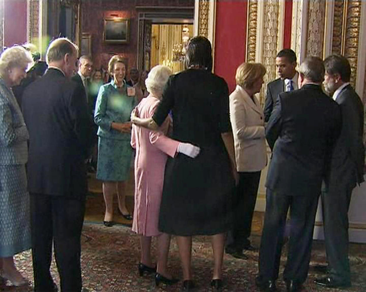 A video grab from television footage shows U.S. first lady Michelle Obama (C) standing with Britain's Queen Elizabeth during a reception for G20 leaders at Buckingham Palace in London April 1, 2009. World leaders arrived in London on Wednesday ahead of a G20 summit meeting under intense pressure to produce a morale-boosting response to the worst economic downturn since the 1930s.  REUTERS/POOL via Reuters Tv   (BRITAIN BUSINESS POLITICS ROYALS) FOR EDITORIAL USE ONLY. NOT FOR SALE FOR MARKETING OR ADVERTISING CAMPAIGNS