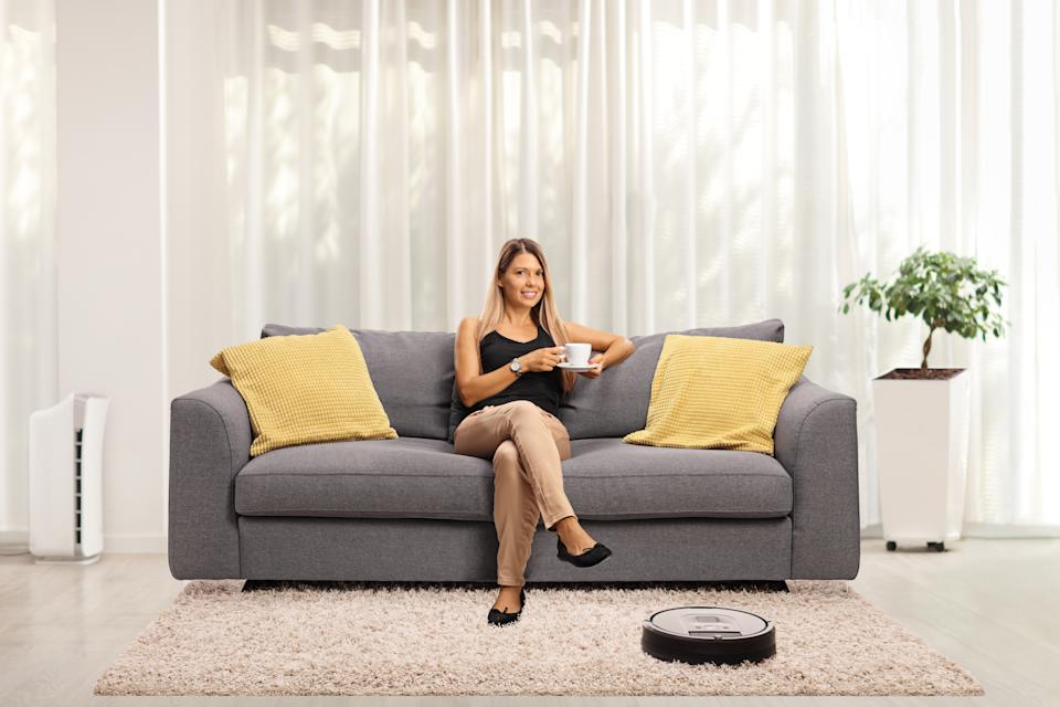 Robotic vacuum cleaner vacuuming a carpet in a living room and a young woman drinking coffee on a sofa