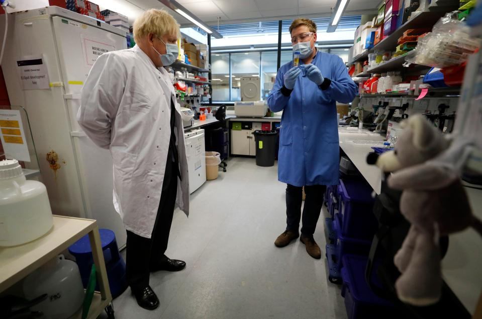 Britain's Prime Minister Boris Johnson (L) looks on during a visit to the Jenner Institute in Oxford, central England, on September 18, 2020, where the Prime Minister toured the laboratory and met scientists who are leading the covid-19 vaccine research. - Millions more people in northern and central England faced new restrictions over a surge in coronavirus cases, the British government announced on Friday, as it warned another national lockdown could be imminent. (Photo by Kirsty Wigglesworth / POOL / AFP) (Photo by KIRSTY WIGGLESWORTH/POOL/AFP via Getty Images)
