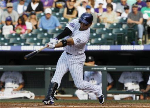 Colorado Rockies' Carlos Gonzalez follows through with his swing after connecting for a solo home run against the Los Angeles Dodgers in the first inning of a baseball game in Denver, Wednesday, July 3, 2013. (AP Photo/David Zalubowski)