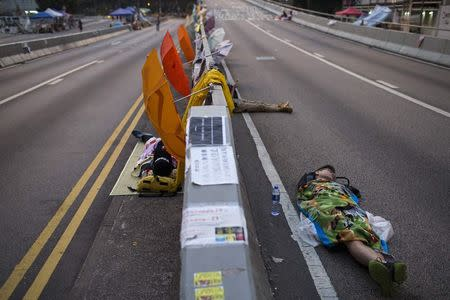 Protesters of the Occupy Central movement sleep on a main road leading to the financial Central district being blocked at dawn, in Hong Kong October 7, 2014. REUTERS/Tyrone Siu