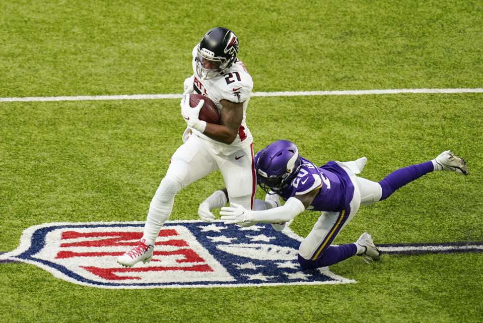 Atlanta Falcons running back Todd Gurley II (21) runs from Minnesota Vikings cornerback Jeff Gladney (20) during the first half of an NFL football game, Sunday, Oct. 18, 2020, in Minneapolis. (AP Photo/Charlie Neibergall)