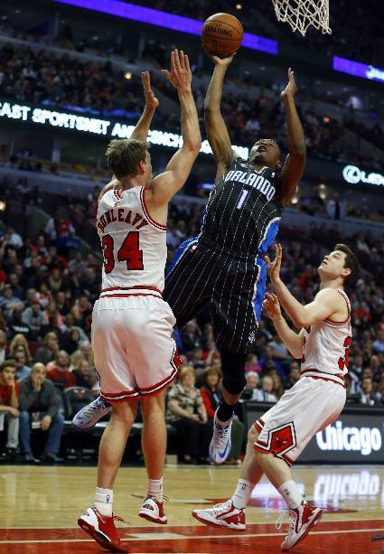 Orlando Magic guard Doron Lamb (1) shoots between Chicago Bulls forward Mike Dunleavy (34) and guard Jimmer Fredette, right, during the first half of an NBA basketball game Monday, April 14, 2014, in Chicago. (AP Photo/Jeff Haynes)
