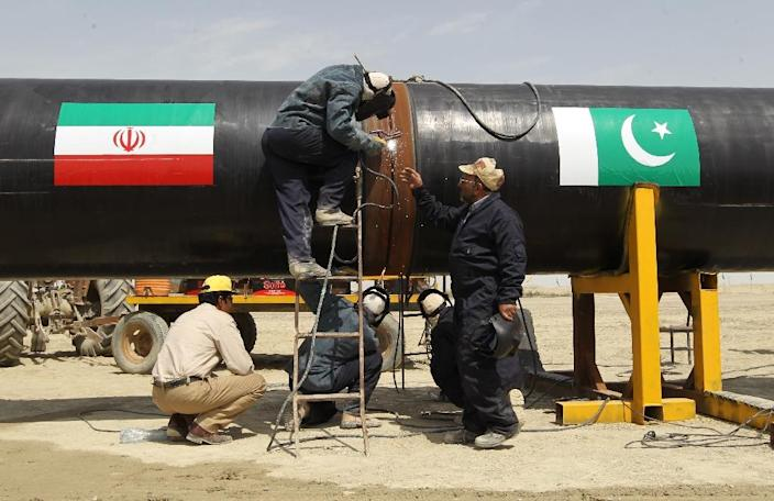 Iranian labourers work on a section of a pipeline - adorned with Iranian (L) and Pakistan (R) flags after a pipeline project was launched in the Iranian border city of Chah Bahar in 2013 (AFP Photo/Atta Kenare)
