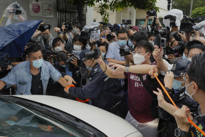 Photographers surround a van which is carrying Agnes Chow, a prominent pro-democracy activist who was sentenced to jail last year for her role in an unauthorized protest, after she was released in Hong Kong Saturday, June 12, 2021. Chow rose to prominence as a student leader in the now defunct Scholarism and Demosisto political groups, alongside other outspoken activists such as Joshua Wong and Ivan Lam. (AP Photo/Vincent Yu)