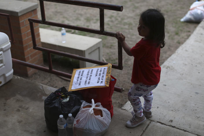 A chid stands next to her family's belongings as they wait for transportation at Our Lady of Guadalupe Catholic Church in McAllen, Texas, on Palm Sunday, March 28, 2021. U.S. authorities are releasing migrant families at the border without notices to appear in immigration court, and sometimes without any paperwork at all. (AP Photo/Dario Lopez-Mills)