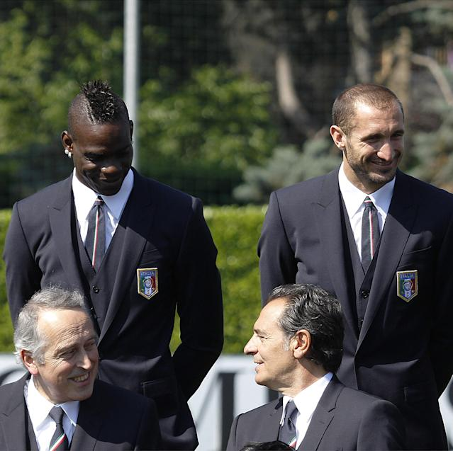 Italy forward Mario Balotelli, background left, flanked by his teammate Giorgio Chiellini, speak with Italy coach, Cesare Prandelli, foreground right, and Giancarlo Abete, president of the Italian Soccer Federation, at the Coverciano center, near Florence, Italy, Tuesday, June 3, 2014. (AP Photo/Fabrizio Giovannozzi)