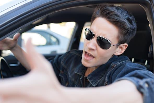 irritated young man driving a...
