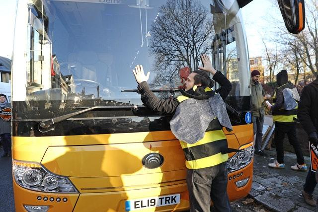 A protester glues himself on to the Liberal Democrats' battle bus