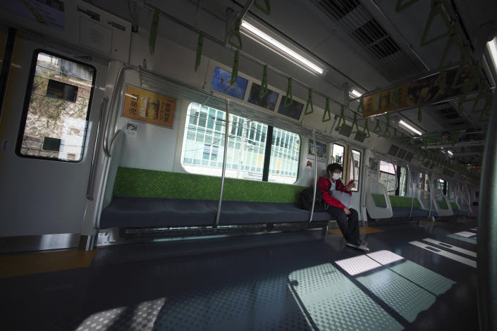 A man with protective mask rides an empty train Wednesday, April 8, 2020, in Tokyo. Japanese Prime Minister Shinzo Abe declared a state of emergency yesterday for Tokyo and six other prefectures to ramp up defenses against the spread of the coronavirus. (AP Photo/Eugene Hoshiko)