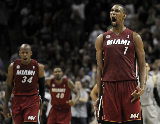 Miami Heat's Chris Bosh (1) yells after scoring the winning 3-pointer with 1.9 seconds left in an NBA basketball game against the San Antonio Spurs, Sunday, March 31, 2013, in San Antonio. Ray Allen (34) and Udonis Haslem (40) also celebrate the play. Bosh scored 23 points as Miami won 88-86. (AP Photo/Darren Abate)
