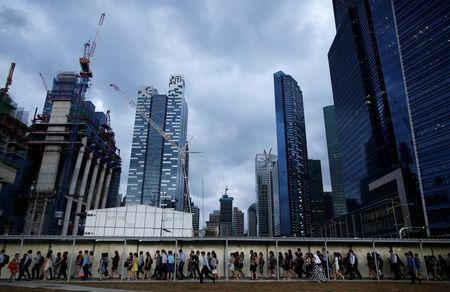 Office workers walk to the train station during evening rush hour in the financial district of Singapore