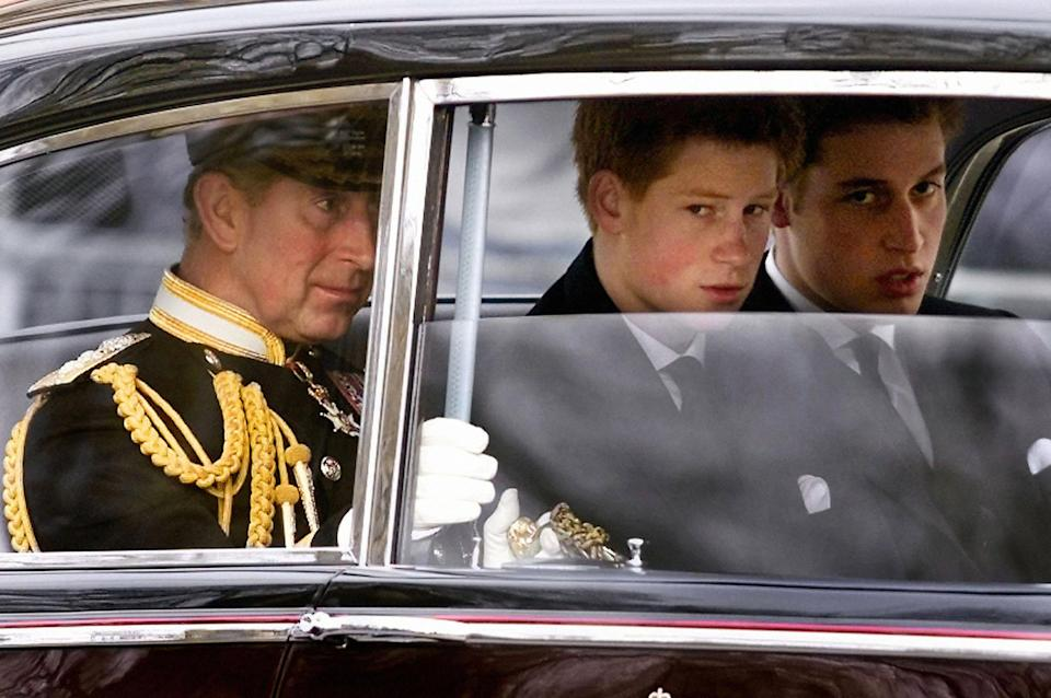 Prince Charles (L) and his sons  Prince Harry (C) and Prince William arrive at Westminster Hall before following the gun carriage carrying coffin of the Queen Mother en-route to Westminster Abbey 09 April 2002 for the Queen Mother's funeral service.  The funeral is the culmination of more than a week of mourning for the royal matriarch, who died March 30 at the age of 101.   AFP PHOTO WPA POOL GERRY PENNY (Photo credit should read GERRY PENNY/AFP via Getty Images)