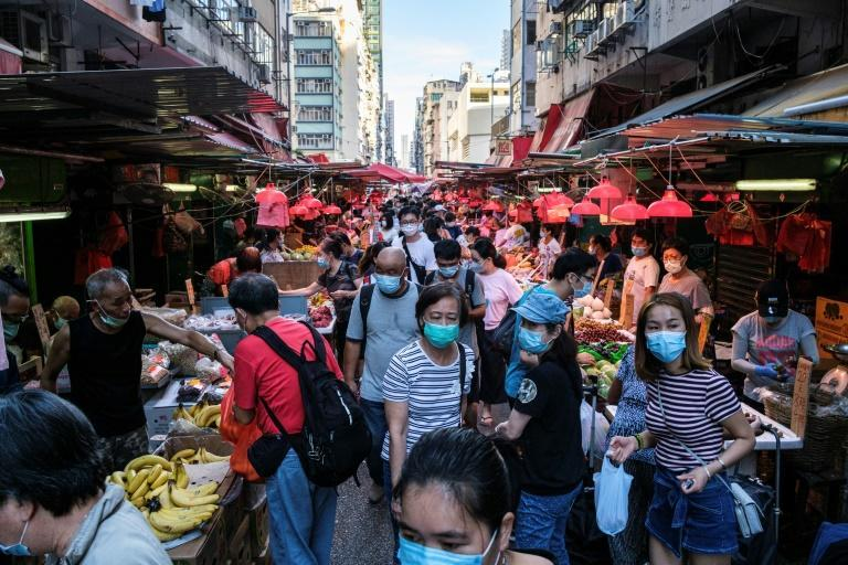 People shop for fruits and vegetables at a street market in Hong Kong