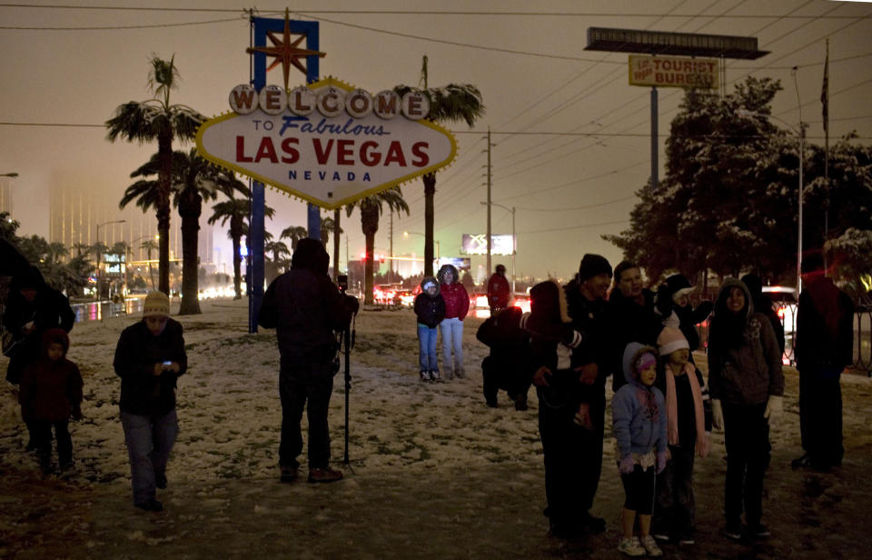 """Tourists and locals stop by the famous """"Welcome to Fabulous Las Vegas, Nevada"""" sign as snow falls December 17, 2008. (PHOTO: REUTERS/Las Vegas Sun/Tiffany Brown)"""