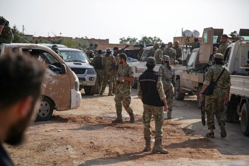 Turkey-backed Syrian fighters gather on a road between the northern Syrian towns of Tal Abyad and Kobani on October 22, 2019, hours before a deadline for the withdrawal of Kurdish fighters from parts of Syria under a US-brokered deal. - President Recep Tayyip Erdogan today threatened to resume Turkey's military offensive in Syria