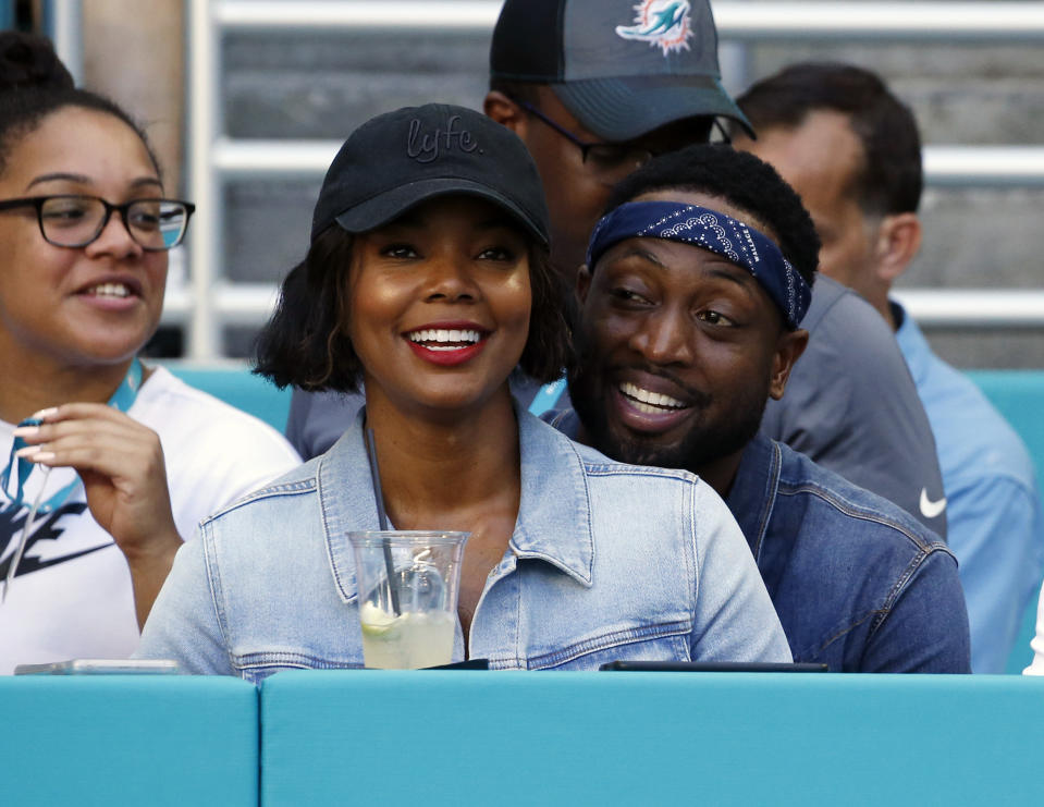 FILE - In this Sunday, Oct. 14, 2018 file photo, Miami Heat player Dwyane Wade and his wife Gabrielle Union-Wade acknowledge the cheers from the crowd during the second half of an NFL football game between the Miami Dolphins and the Chicago Bears in Miami Gardens, Fla. Miami Heat star Dwyane Wade and his wife Gabrielle Union-Wade have a baby. The couple on Thursday, Nov. 8, 2018 announced they've welcomed a baby girl into the world. (AP Photo/Joel Auerbach, File)