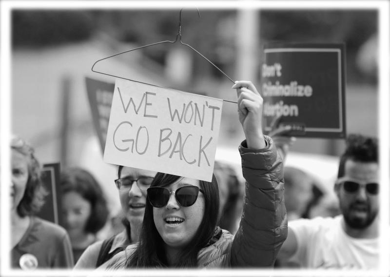 """Hillary Namba holds a wire coat hanger and a sign that reads """"We Won't Go Back"""" during a protest in Seattle in 2018. (Photo:Ted S. Warren/AP)"""