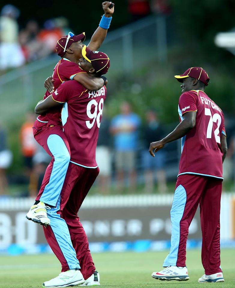HAMILTON, NEW ZEALAND - JANUARY 08:  Jason Holderof the West Indies (C) celebrates his runout of Kyle Mills of New Zealand during game five of the One Day International Series between New Zealand and the West Indies at Seddon Park on January 8, 2014 in Hamilton, New Zealand.  (Photo by Phil Walter/Getty Images)