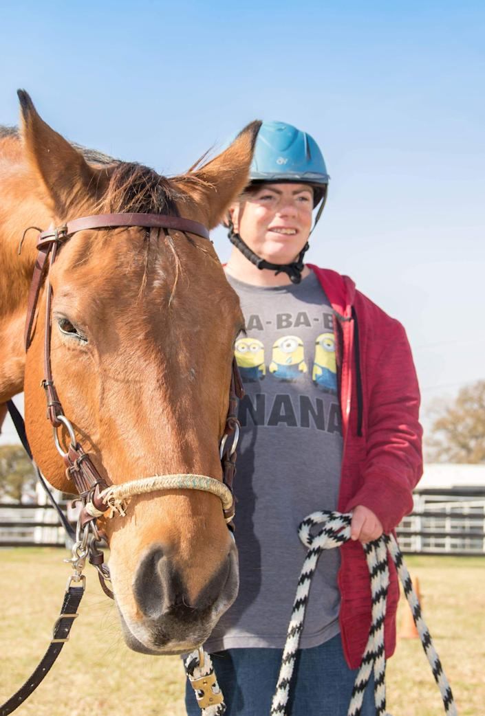 Stephen Gersuk, who is 40 and lives at the Denton State Supported Living Center, stands by a horse at a therapeutic riding center in Aubrey, TX. Staffers from the center take Gersuk to the riding center every Friday.
