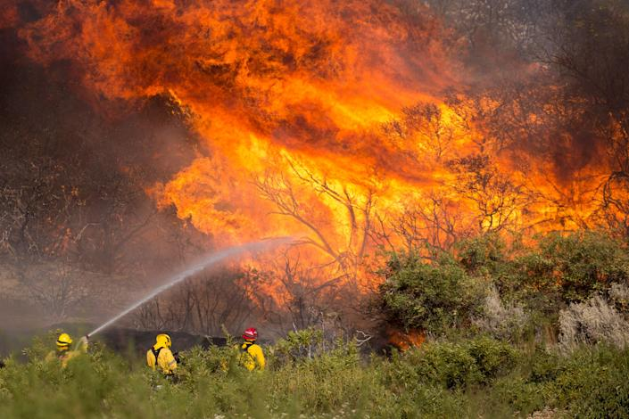 Firefighters battle the Apple Fire in Banning, Calif., on Sunday. (Photo: AP Photo/Ringo H.W. Chiu)