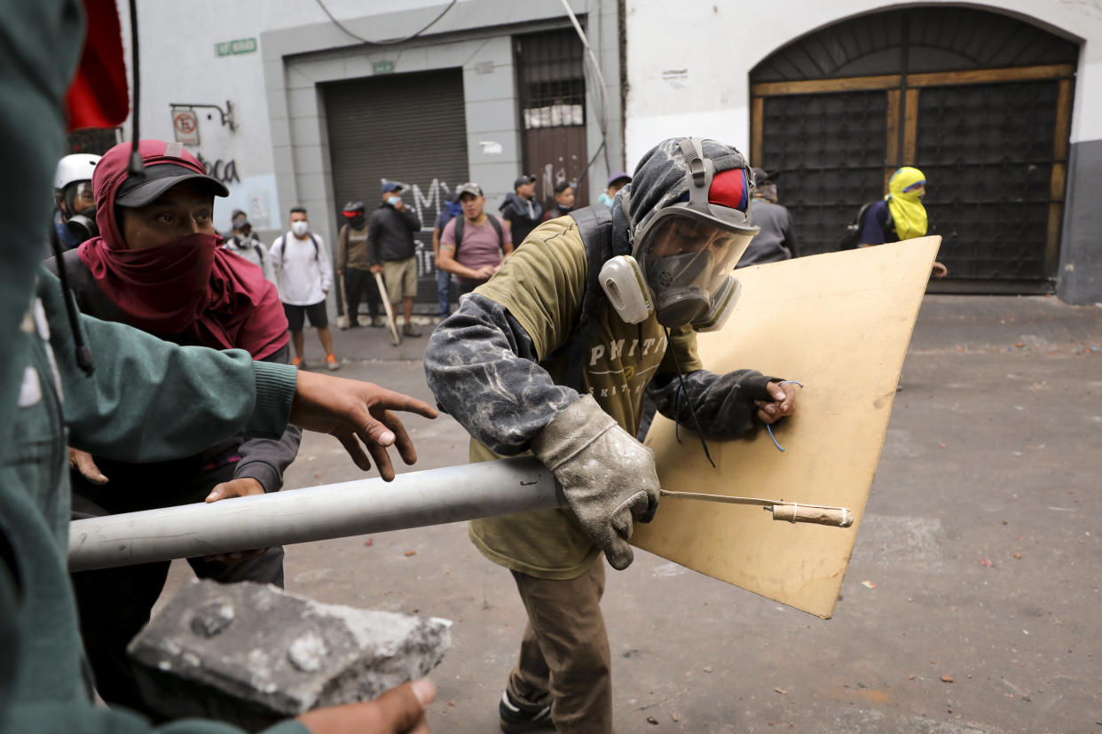 Protesters prepare a makeshift firework launcher during clashes with security forces in downtown Quito, Ecuador, Oct. 8, 2019. (Photo: Fernando Vergara/AP)