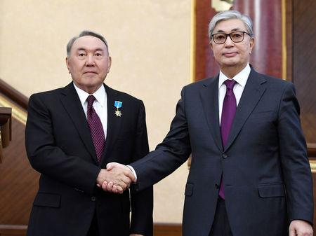 Acting President of Kazakhstan Tokayev shakes hands with his predecessor Nazarbayev during a joint session of the houses of parliament in Astana
