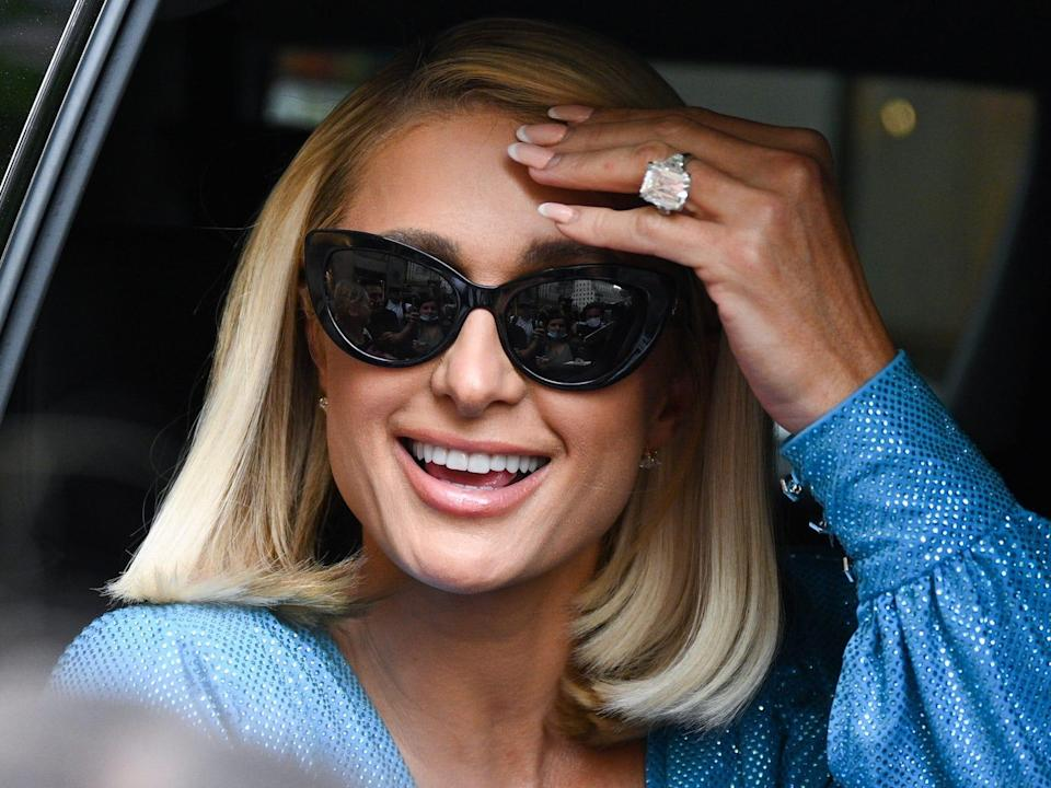 Paris Hilton wears sunglasses and raises a hand to her forehead from a car, showing off her engagement ring.
