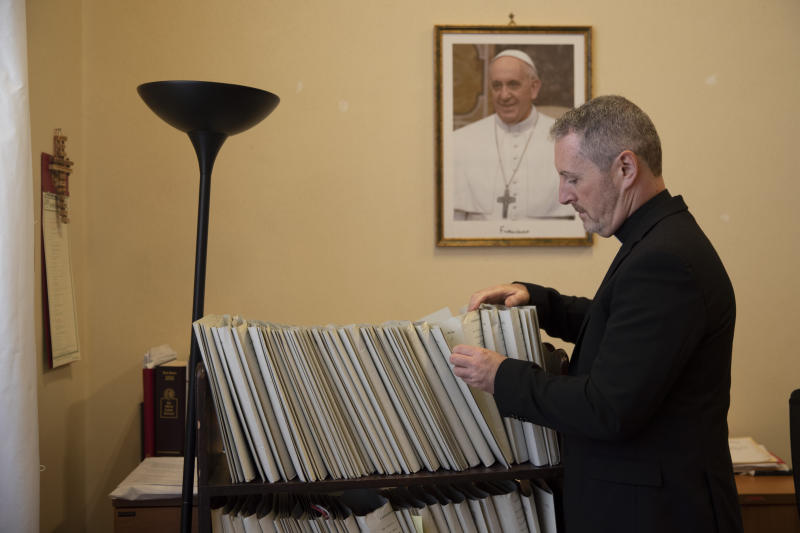 In this Monday, Dec. 9, 2019 photo, Monsignor John Kennedy, the head of the Congregation for the Doctrine of the Faith discipline section, looks through files at his office during an interview at the Vatican. The Vatican office responsible for processing clergy sex abuse complaints has seen a record 1,000 cases reported from around the world this year, including from countries it had not heard from before, suggesting that the worst may be yet to come in a crisis that has plagued the Catholic Church. (AP Photo/Alessandra Tarantino)