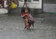 <p>A Filipino girl is carried along a flooded road in suburban Mandaluyong, east of Manila, Philippines, as monsoon downpours intensify while Typhoon Nepartak exits the country on Friday, July 8, 2016. (AP Photo/Aaron Favila) </p>